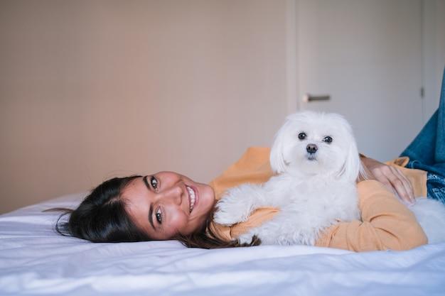 Mujer acostada en la cama con su lindo perro maltés