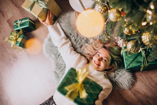 Mujer acostada debajo del árbol de navidad con regalos