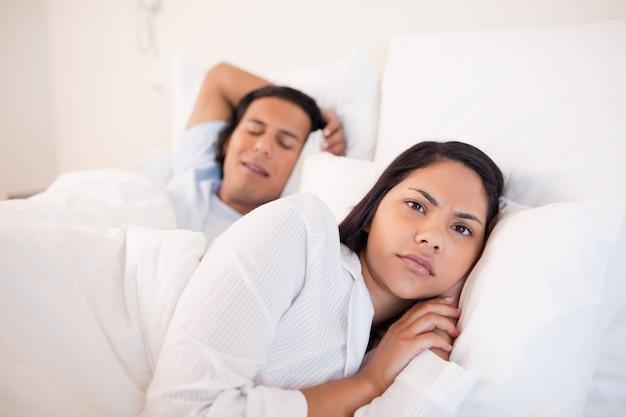 Mujer acostada despierta junto a su novio durmiendo