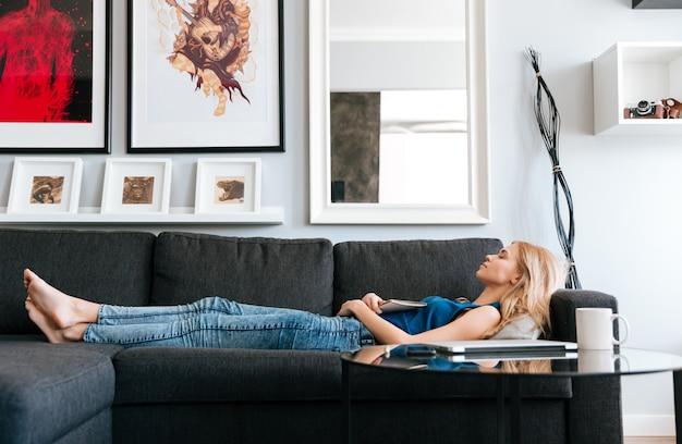 Mujer acostada y durmiendo en el sofá en casa