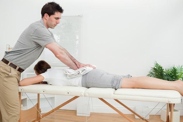 Mujer acostada mientras se le da un masaje con una toalla