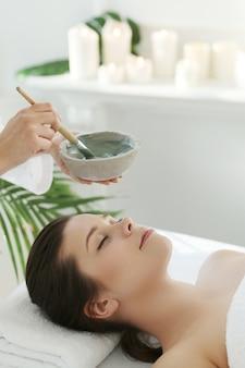 Mujer acostada recibiendo un tratamiento de belleza facial.