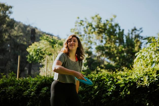 Mujer activa lanzando un friesbee