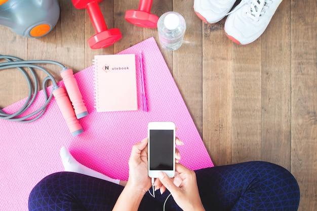 Mujer en activewear utilizando dispositivo móvil. entrenamiento en casa con aparatos inteligentes