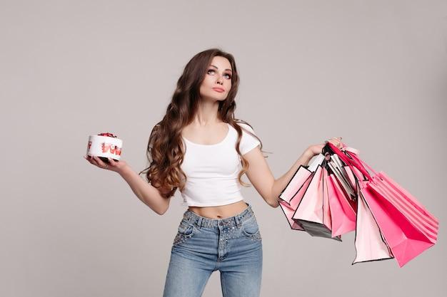 Mujer adicta a las compras con caja de deliciosos dulces y bolsas de compras