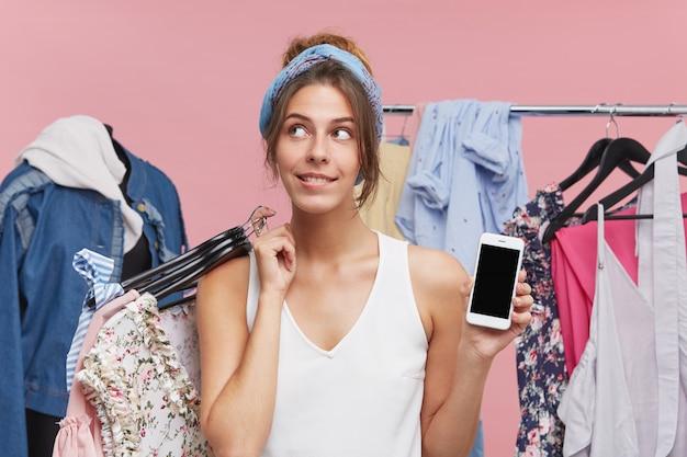 Mujer adicta a las compras de pie en la boutique, tomando muchas perchas con ropa para probarse, mirando con expresión soñadora a un lado, decidiendo qué llevar, manteniendo el teléfono móvil moderno en la otra mano