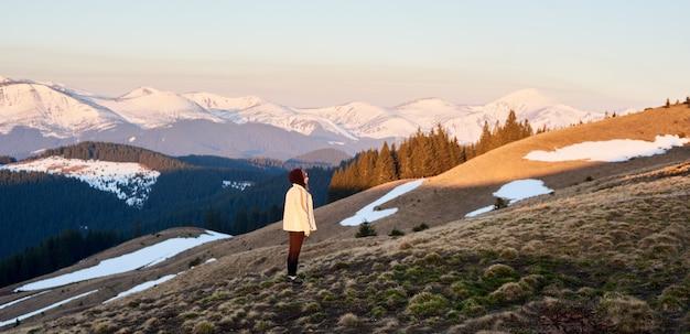 Mujer admirando la vista de las montañas mientras camina