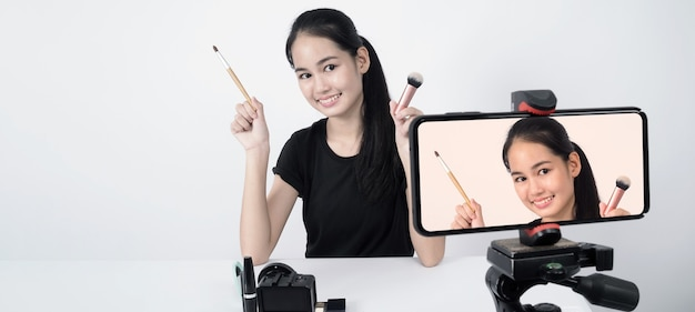 Una mujer adolescente asiática se sienta frente a la cámara y transmite en vivo como una influyente bloguera de belleza o youtuber para revisar o dar consejos sobre cómo maquillarse en casa.