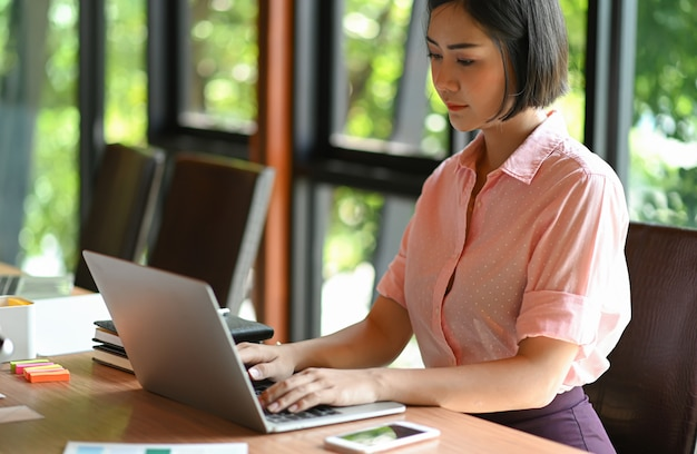 La mujer adolescente asiática está usando una computadora portátil en oficina.