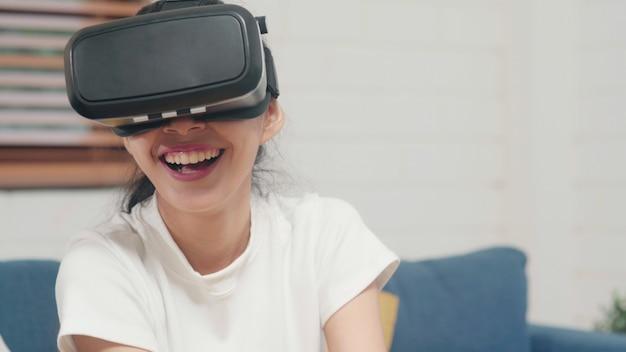 Mujer adolescente asiática usando gafas simulador de realidad virtual jugando videojuegos en la sala de estar
