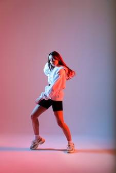 Mujer adolescente bailando hip-hop en un estudio, ropa casual