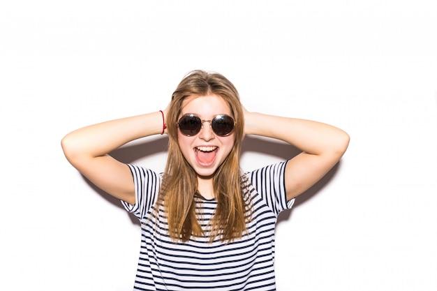 Mujer adolescente casual divertida con gafas de sol de moda gesticular aislado en una pared blanca
