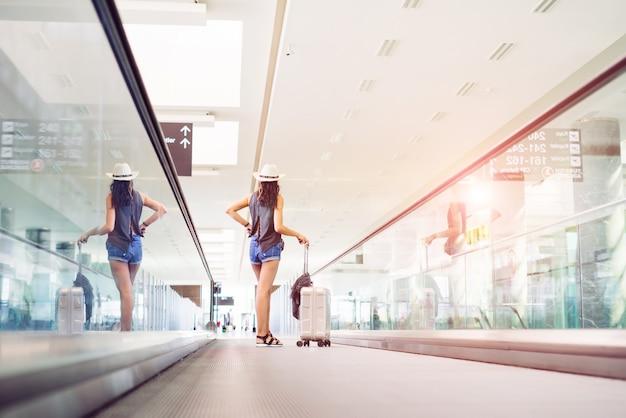 Mujer adolescente joven con equipaje de mano, maleta en escalera mecánica en la terminal del aeropuerto internacional. viajero de vacaciones