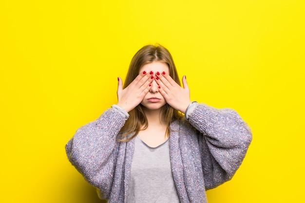 Mujer adolescente joven que cubre sus ojos aislados
