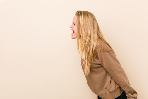 Mujer adolescente linda y natural gritando hacia un espacio de copia