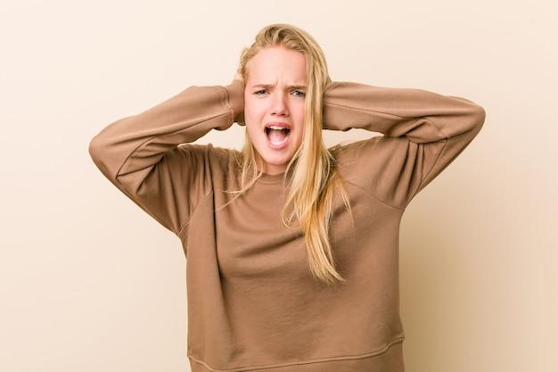 Mujer adolescente linda y natural que cubre los oídos con las manos tratando de no escuchar un sonido demasiado fuerte.