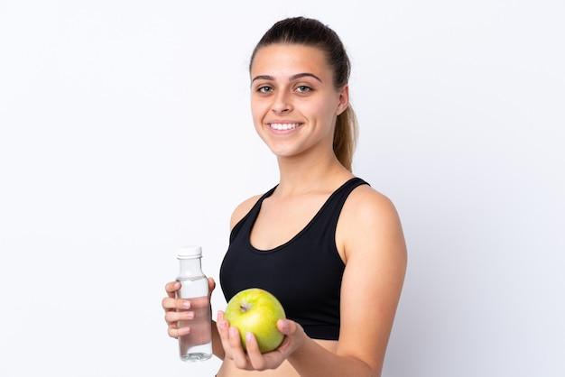 Mujer adolescente con una manzana y una botella de agua sobre una pared aislada