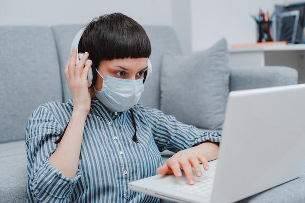Mujer adolescente con máscara médica contra virus sentado piso sala de estar sofá estudiante estudiando en casa portátil haciendo la tarea