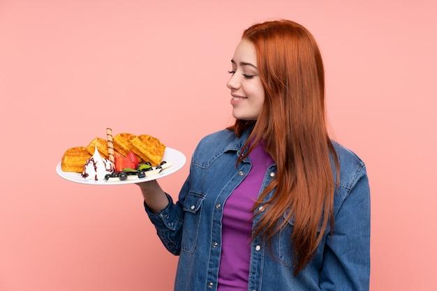Mujer adolescente pelirroja con gofres con expresión feliz