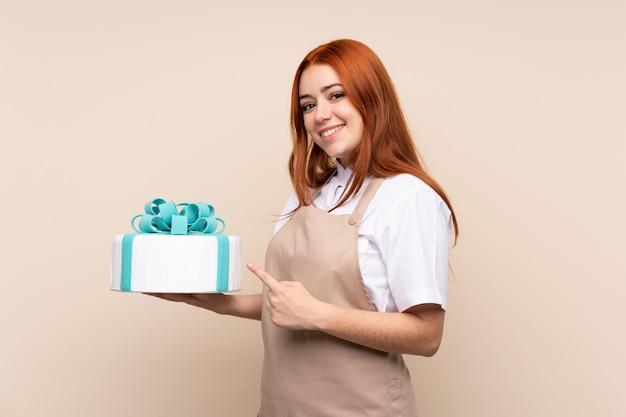 Mujer adolescente pelirroja con un gran pastel y apuntando