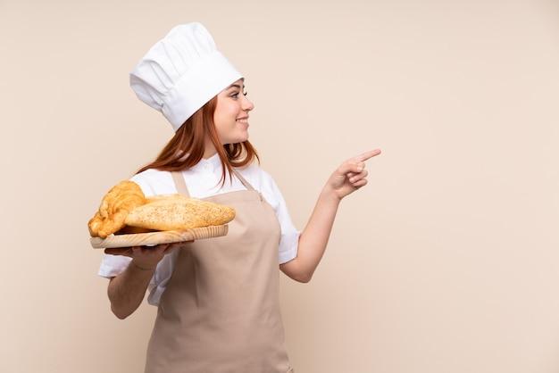 Mujer adolescente pelirroja en uniforme de chef. mujer panadero sosteniendo una mesa con varios panes apuntando hacia un lado para presentar un producto