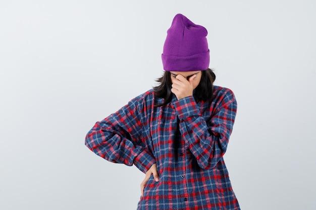 Mujer adolescente poniendo la mano sobre glabela sosteniendo la mano en la cadera mirando molesto