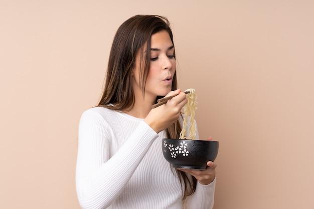 Mujer adolescente sobre pared aislada sosteniendo un tazón de fideos con arena de palillos soplando porque están calientes