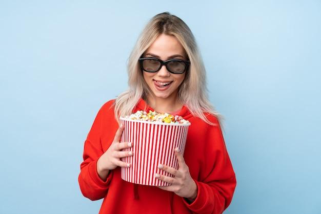 Mujer adolescente sobre pared azul aislada con gafas 3d y sosteniendo un gran cubo de palomitas de maíz