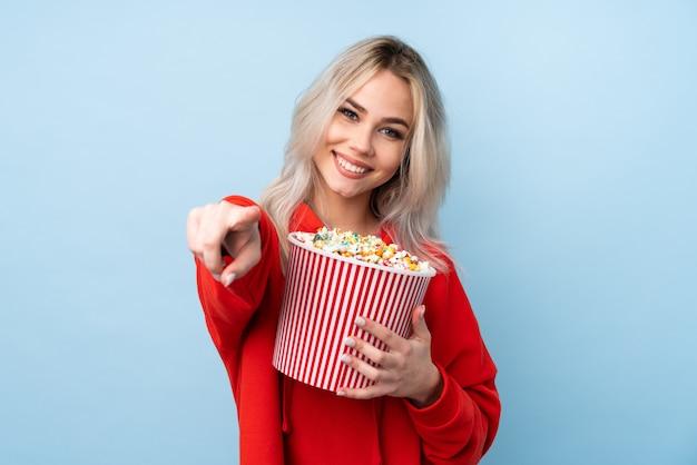 Mujer adolescente sobre pared azul aislada sosteniendo un gran cubo de palomitas de maíz mientras apunta hacia adelante
