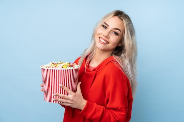 Mujer adolescente sobre pared azul aislada sosteniendo un gran cubo de palomitas de maíz