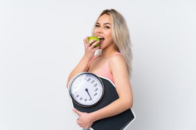 Mujer adolescente sobre pared blanca aislada con máquina de pesaje y con una manzana