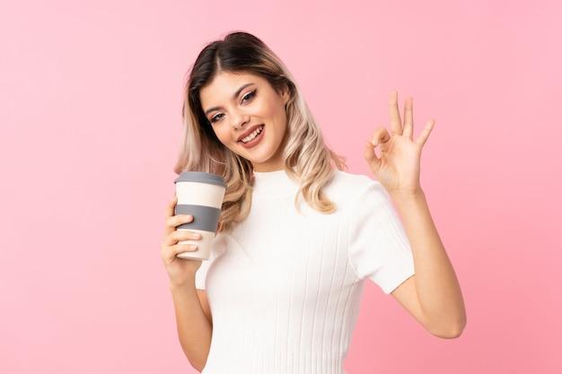 Mujer adolescente sobre rosa aislado sosteniendo café para llevar mientras hace signo de ok