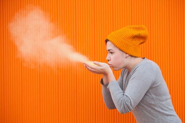 Mujer adolescente soplando una nube de polvo de color sobre una pared naranja