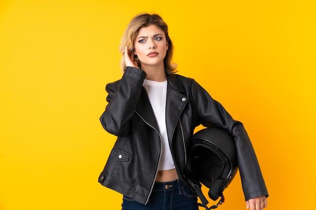 Mujer adolescente sosteniendo un casco de motocicleta aislado en la pared amarilla infeliz y frustrada con algo. expresión facial negativa