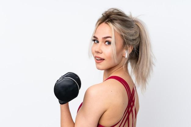 Mujer adolescente sosteniendo gofres sobre pared azul aislada haciendo pesas