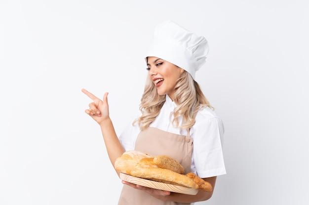 Mujer adolescente en uniforme de chef. panadero de sexo femenino que sostiene una tabla con varios panes sobre el dedo acusador blanco aislado al lado