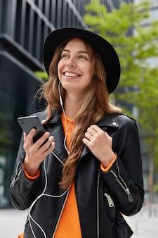 Mujer adorable optimista escucha radio en línea, disfruta de la canción en auriculares electrónicos