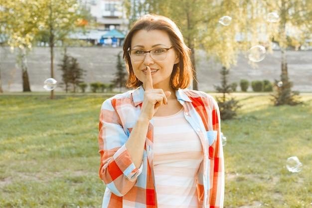 Mujer adulta al aire libre muestra signo en silencio
