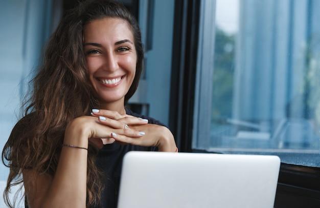 Mujer adulta autónoma que trabaja desde casa, usando una computadora portátil y sonriendo felizmente a la cámara.