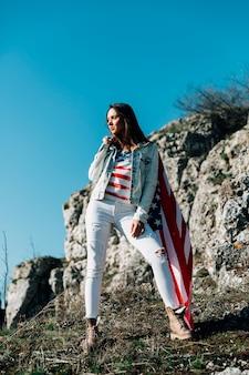 Mujer adulta con bandera americana en la naturaleza.