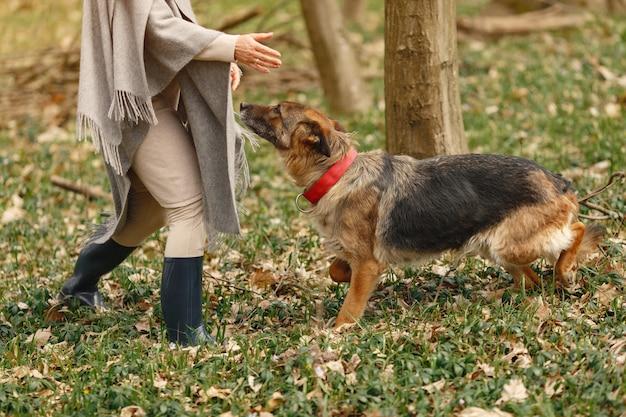 Mujer adulta en un bosque de primavera con perro