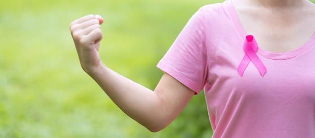 Mujer adulta con camiseta rosa y cinta rosa para apoyar a las personas que viven y están enfermas