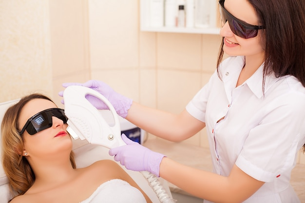 Mujer adulta con depilación láser en salón de belleza profesional