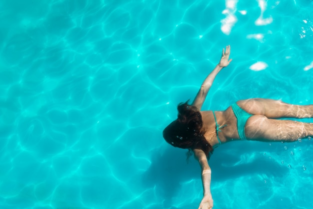 Mujer adulta flotando bajo el agua de la piscina brillante