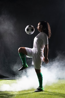 Mujer adulta en forma jugando con fútbol