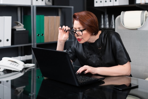Mujer adulta con gafas de mano y mirando a través de ellas en el monitor en la oficina