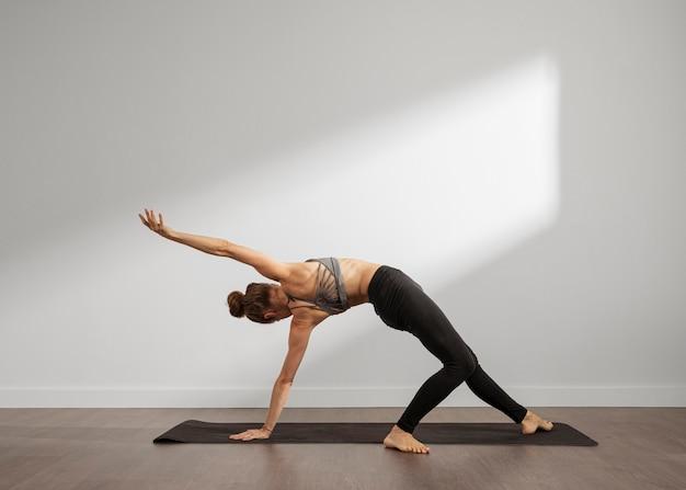 Mujer adulta haciendo yoga en casa