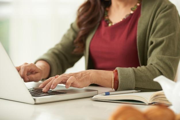 Mujer adulta irreconocible trabajando en la computadora portátil sentado en la mesa en casa