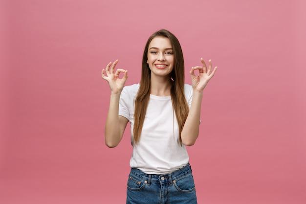 Mujer adulta joven atractiva que muestra la muestra aceptable