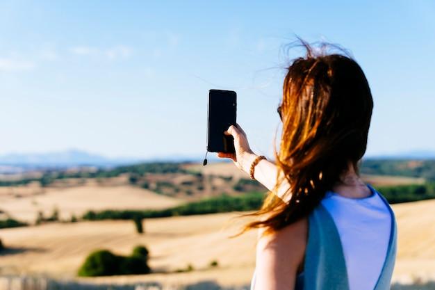 Mujer adulta joven desde atrás tomando una foto de la puesta de sol con el teléfono inteligente